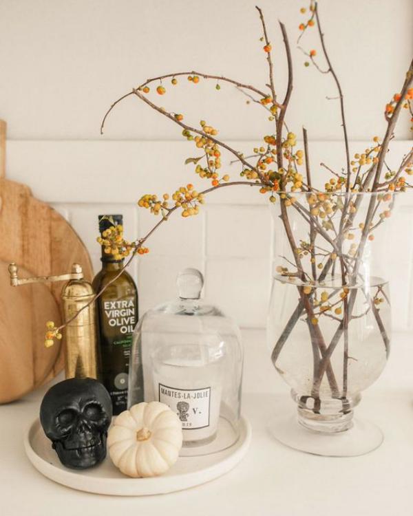 minimalistische Halloween Deko weißer Kürbis schwarzer Totenkopf Flaschen Vase mit Zweigen