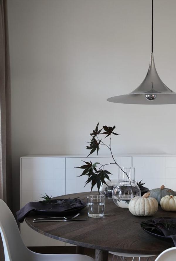 minimalistische Halloween Deko wenig Tischschmuck kleine Kürbisse Vase mit Zweig schwarze Servietten